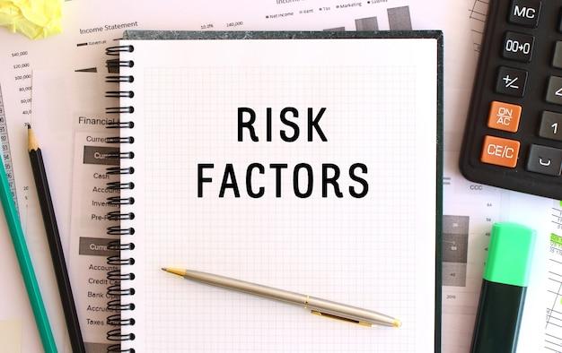 Notatnik z tekstem czynniki ryzyka na biurku, w pobliżu materiałów biurowych