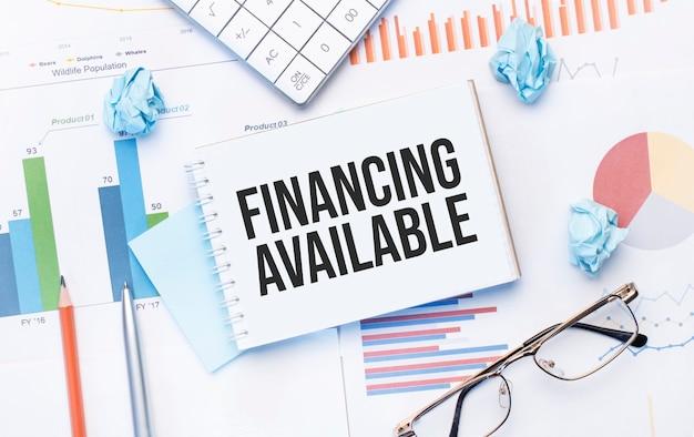 Notatnik z tekstem dostępne finansowanie na wykresach biznesowych i długopis, biznes