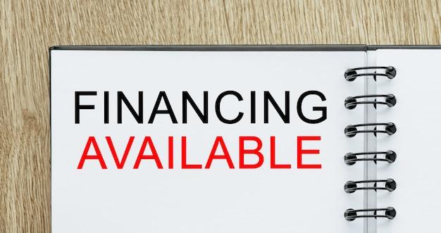 Notatnik z tekstem finansowanie dostępny na drewnianym biurku. koncepcja biznesu i finansów