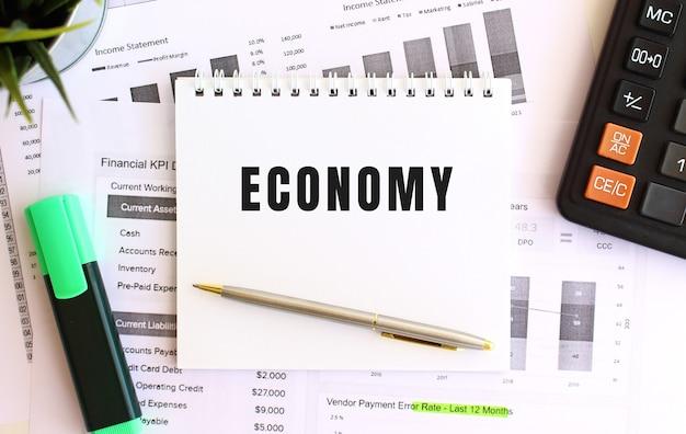 Notatnik z tekstem gospodarka na białym tle, w pobliżu markera, kalkulatora i materiałów biurowych. pomysł na biznes.