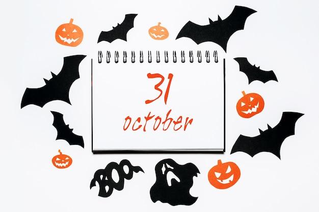 Notatnik z tekstem halloween 31 października na białej przestrzeni z nietoperzami, dyniami i duchami