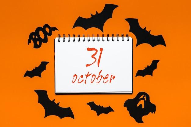 Notatnik z tekstem halloween 31 października na białym i pomarańczowym tle z nietoperzami, dyniami i duchami
