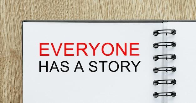 Notatnik z tekstem każdy ma historię na drewnianym biurku. koncepcja biznesu i finansów