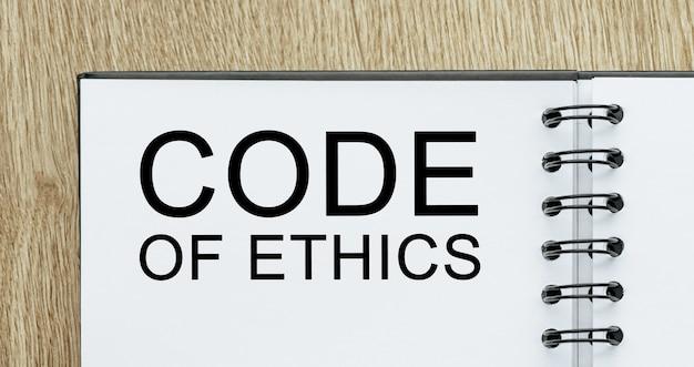 Notatnik z tekstem kodeks etyki na drewnianym biurku. koncepcja biznesu i finansów