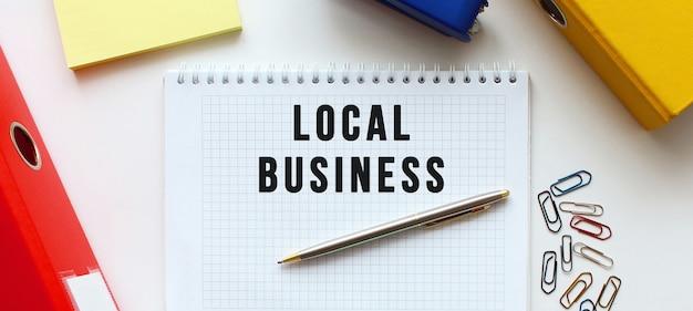 Notatnik z tekstem lokalny biznes na białym tle, w pobliżu folderu dokumentów i materiałów biurowych. pomysł na biznes.