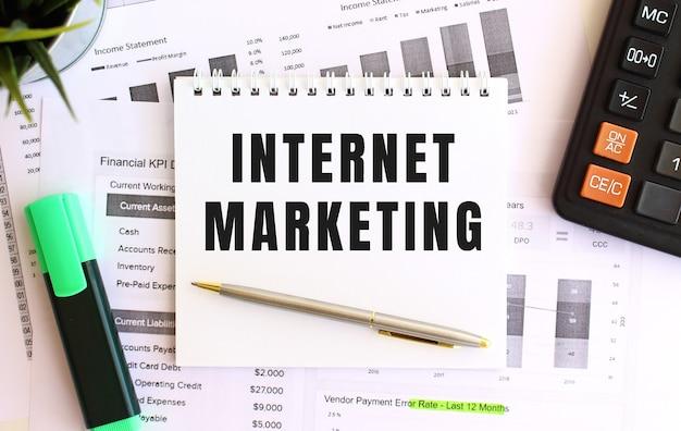 Notatnik z tekstem marketing internetowy na białym tle, obok markera, kalkulatora i materiałów biurowych