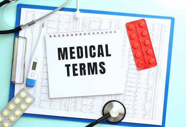 Notatnik z tekstem medical warms leży na medycznym schowku ze stetoskopem i tabletkami na niebieskim tle.