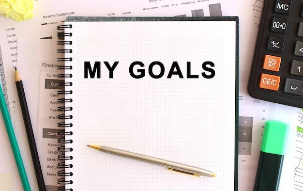 Notatnik z tekstem moje cele w pobliżu kalkulatora i materiałów biurowych.