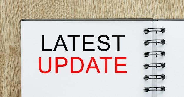 Notatnik z tekstem najnowsza aktualizacja na drewnianym biurku. koncepcja biznesu i finansów