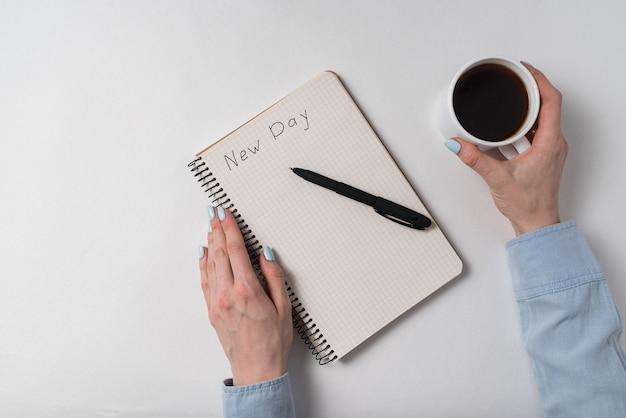 Notatnik z tekstem nowy dzień i mężczyzna pije kawę