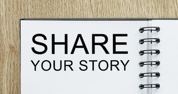 Notatnik z tekstem podziel się swoją historią na drewnianym biurku. koncepcja biznesu i finansów