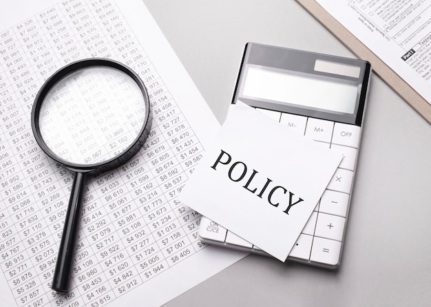 Notatnik z tekstem polityka arkusz białego papieru na notatki, kalkulator, lupa