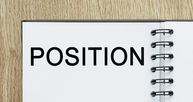 Notatnik z tekstem position na drewnianym biurku. koncepcja biznesu i finansów