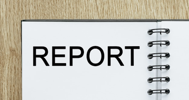 Notatnik z tekstem raport na drewnianym biurku. koncepcja biznesu i finansów
