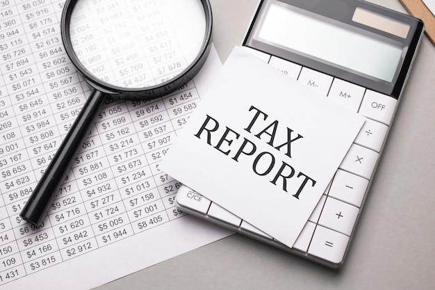 Notatnik z tekstem raport podatkowy arkusz białego papieru na notatki