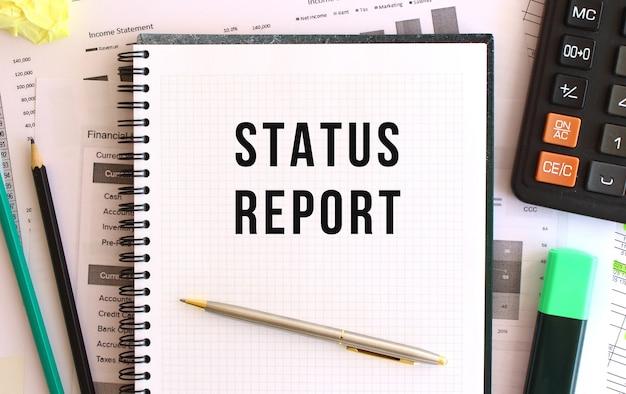Notatnik z tekstem raport stanu na biurku, w pobliżu materiałów biurowych.