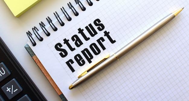 Notatnik z tekstem raport statusu, obok kalkulator i żółte notesy.