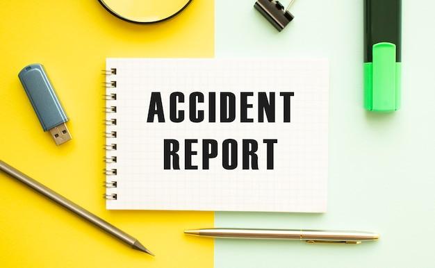 Notatnik z tekstem raport z wypadku na biurku z artykułami biurowymi