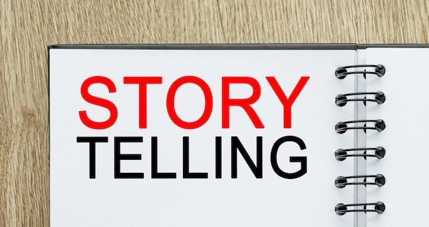 Notatnik z tekstem storytelling to najlepszy marketing na drewnianym biurku. koncepcja biznesu i finansów