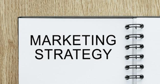 Notatnik z tekstem strategia marketingowa na drewnianym biurku. koncepcja biznesu i finansów