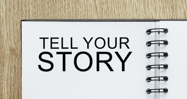 Notatnik z tekstem tell your story na drewnianym biurku. koncepcja biznesu i finansów