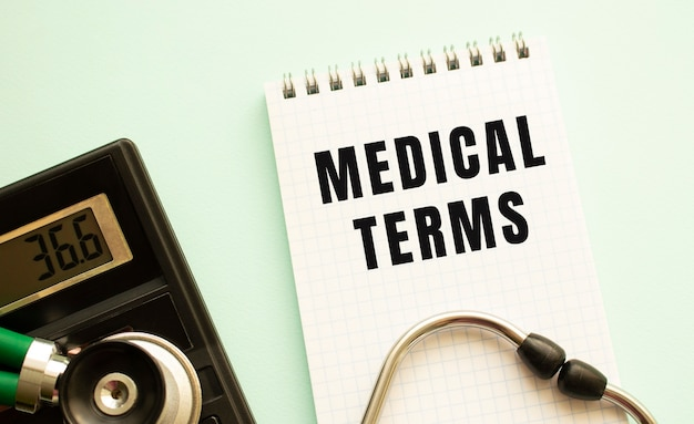 Notatnik z tekstem warunki lekarskie, kalkulator i stetoskop na białym tle. pojęcie medyczne.