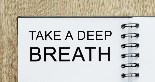 Notatnik z tekstem weź głęboki oddech na drewnianym biurku. koncepcja biznesu i finansów
