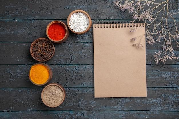 Notatnik z widokiem z góry i notatnik do przypraw między różnymi kolorowymi przyprawami i gałęziami na stole