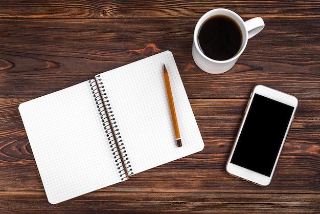 Notatnik z żółtym ołówkiem i kawą na drewnianym tle. cele na nowy rok. koncepcja planowania i harmonogramu. lista rzeczy do zrobienia.