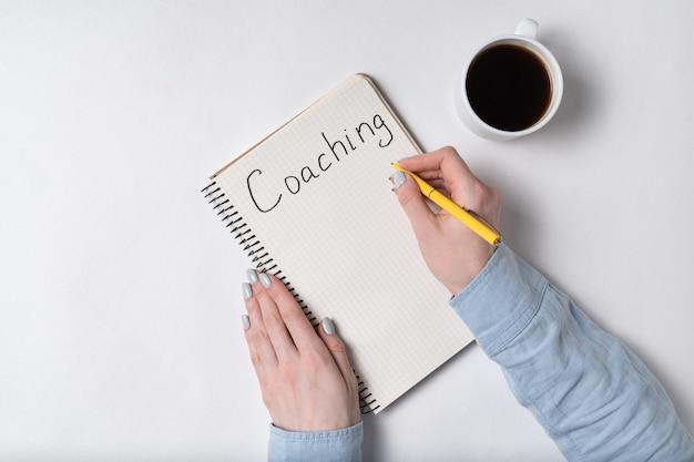 Notatnik ze słowem coaching. kobiet ręki i filiżanka kawy na białym tle. widok z góry