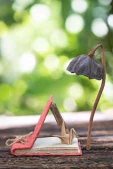 Notatnik ze starego papieru, drewniany ołówek, papierowa lampa ptaszek z suszonego lotosu w naturze.