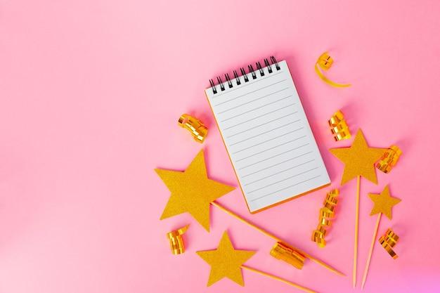 Notatnik ze złotymi wstążkami i złotymi gwiazdkami na różowej powierzchni