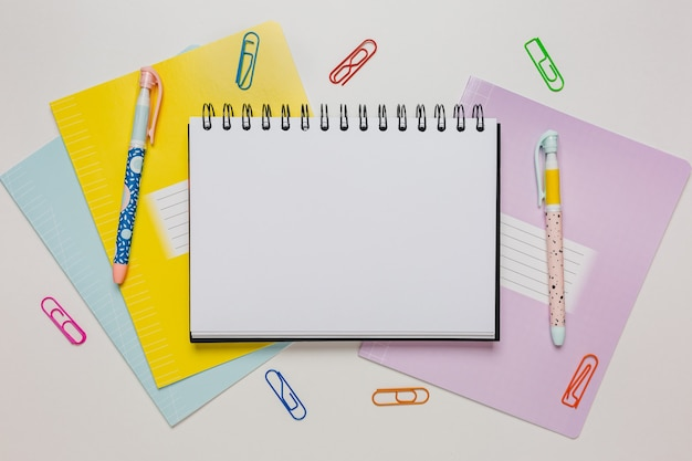 Notatnik, zeszyt i długopis na biurku. makiety w biurze kopii przestrzeni na białym tle. powrót do szkoły