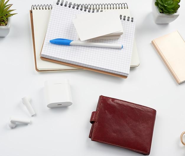 Notatniki, długopis, stos wizytówek, brązowy skórzany portfel i power bank