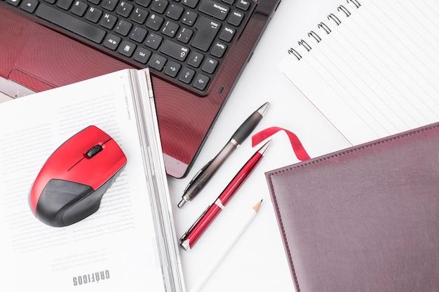 Notatniki i pióra w pobliżu laptopa i myszy