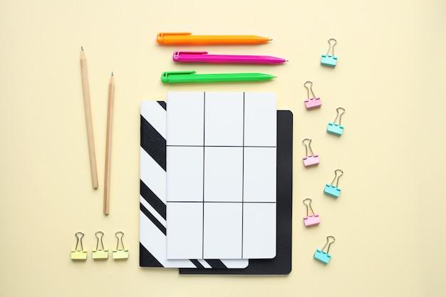 Notatniki, ołówki, pióro, segregatory na biege tle. odgórny widok na różnorodnym materiały na biurku.