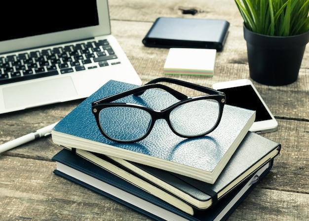 Notatniki ułożone na stole biurowym z okularami