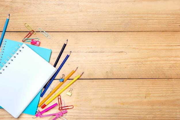 Notatniki z szkolnymi dostawami i materiały na drewnianym stołowym tle