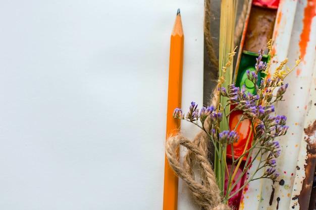 Noteboo z farbami akwarelowymi, kwiatami i ołówkiem