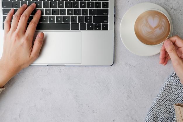 Notebook do laptopa i kawa z latte art. szczęśliwa poranna praca.