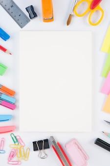 Notebook i szko? y lub narz? dzi biurowych na bia? ym tle i
