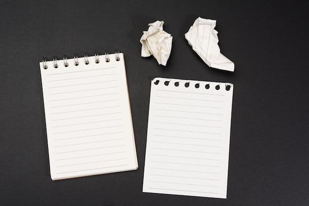 Notebook z białymi arkuszami w linii na czarnym tle, z bliska
