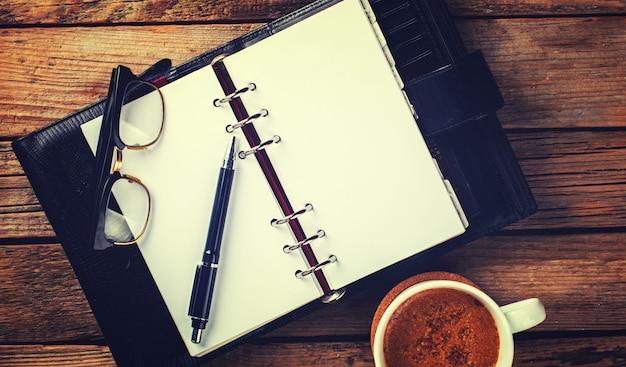 Notebook z piórem, szklankami i kawą