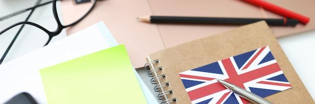 Notebooki, długopisy i laptop są na stole zdobywając edukację za granicą
