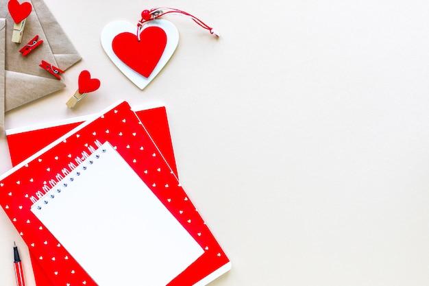Notebooki i koperty do szkoły lub biura w kolorze czerwonym na białym stole z miejsca na kopię.