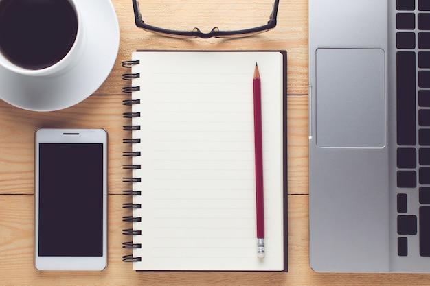 Notepad, smartphone, pióro i filiżanka kawy na drewno stole