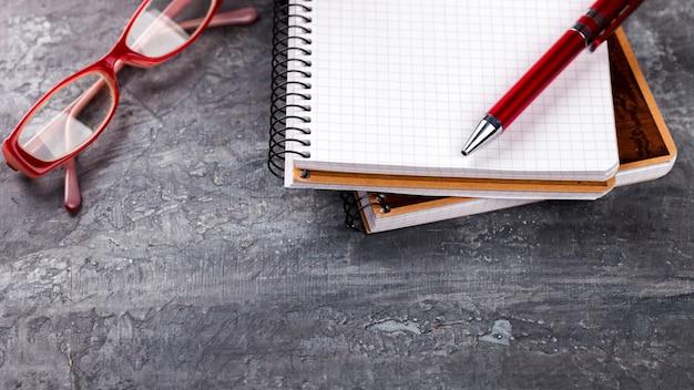 Notepad z piórem, szkło biznesu pojęcie