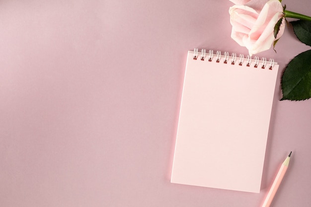Notes na jasnoróżowej powierzchni z różową różą