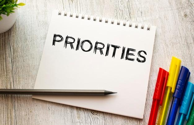 Notes na sprężynie z napisem priorytety na białej prześcieradle leży na drewnianym stole z kolorowymi długopisami