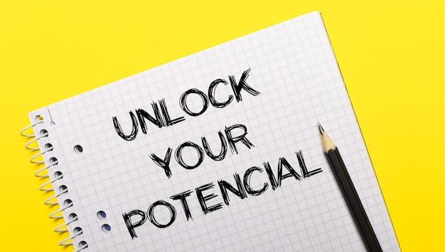 Notes w kolorze białym z napisem unlock your potential napisanym czarnym ołówkiem na jasnożółtym tle